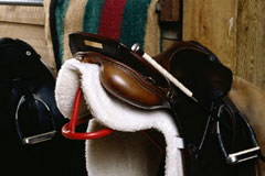 leather saddle atop a saddle rack