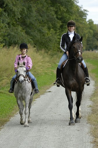 mother and daughter on a trail ride with horse and pony